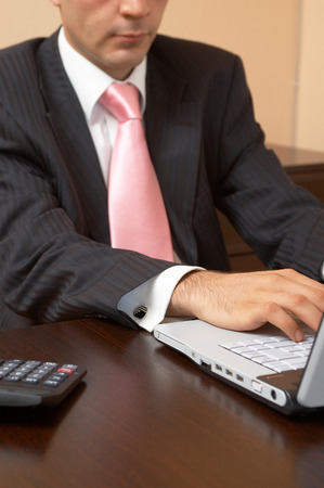 highend: young businessman with a laptop and calculator at the office