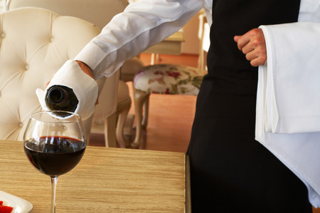 waiter serving red wine with bottle at the restaurant Stock Photo