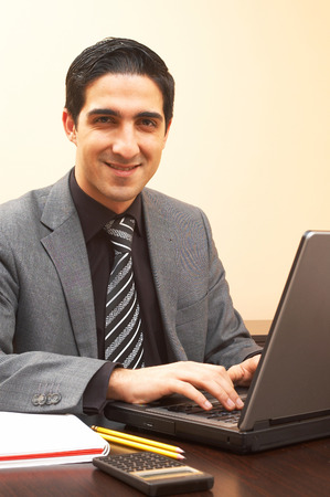 highend: young businessman with a laptop at the office