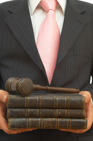 legal concept for business with businessman holding gavel and books