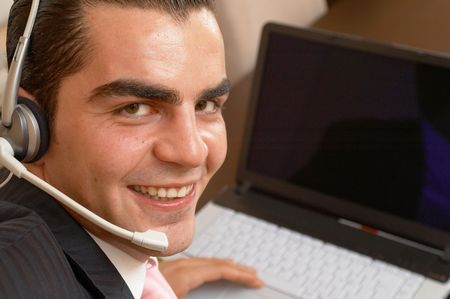 young happy businessman ready to help with a headset and laptop photo