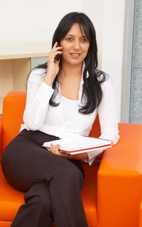 telework: young businesswoman talking with her cell phone at the office