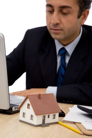 businessman with a house and laptop at the office, shallow dof Stock Photo - 2160903