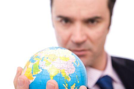 online internet presence: serious businessman holding mini globe on white background