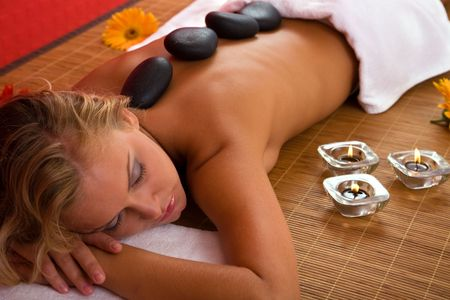 spa concept with a beautiful woman having volcanic stone massage