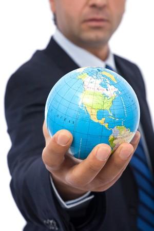 online internet presence: businessman holding mini globe on white background
