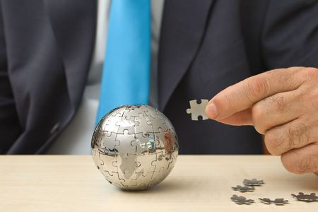 Businessman with a mini puzzle globe   Stock Photo