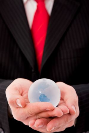 online internet presence: businessman close up with a glass globe, shallow dof  Stock Photo