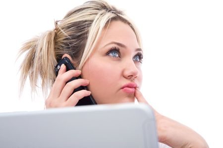 telework: Young businesswoman talking with her cell phone and working with laptop