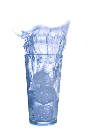 seltzer: Water splashing from glass with ice cubes