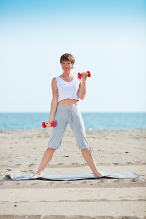 woman doing exercise with dumbell on beach Stock Photo