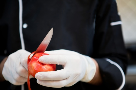 meal preparation: Chef peeling  tomatoes in restaurant kitchen