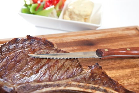 Grilled meat steak with knife in cutting board photo