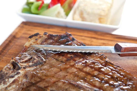 t bone: Grilled T bone  with knife on cutting board