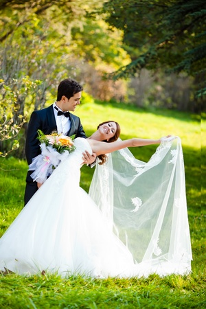 dancing wedding couple at a park on a sunny day photo