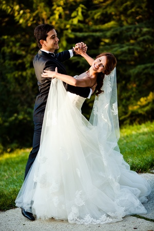 bruidspaar dansen in een park op een zonnige dag Stockfoto