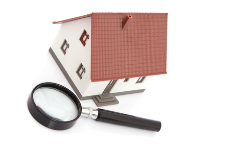 Magnifying glass with dummy of house isolated on white photo