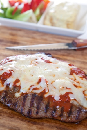 t bone: Grilled T bone steak garnished with cheese and sauce  Stock Photo