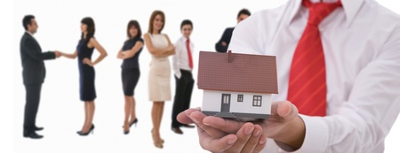 Businesspeople shaking hands and posing with dummy of house Stock Photo