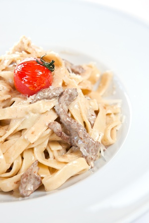 Chicken fettuccine  garnished with cherry photo