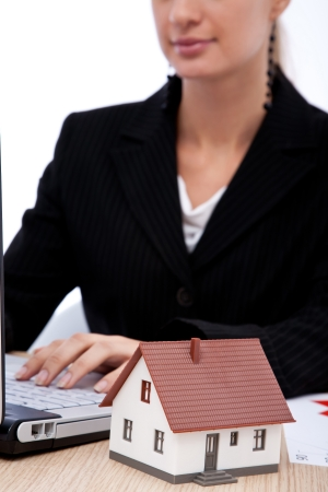 real estate concept with a house; businesswoman and laptop