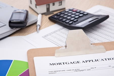 mortgage application form with laptop, phone; calculator and house photo
