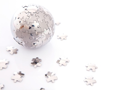 puzzle globe with lots of pieces on white background photo
