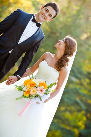 happy bride and groom at a park on their wedding day Stock Photo
