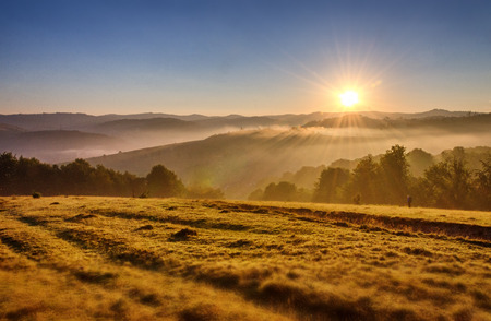 Sunrise with sunbeams in the foggy mountains