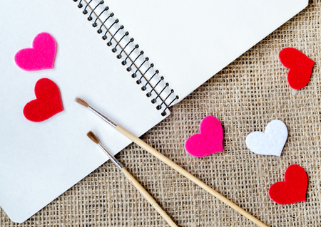 bagging: The paper hearts and notebook with brushes on the sackcloth Stock Photo