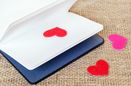 The paper hearts and notebook on the sackcloth