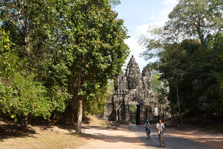 east gate: Locals riding bicycles pass the East Gate of Angkor Thom Siem Reap Cambodia.