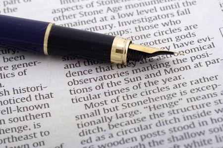 Pen over newspaper close up
