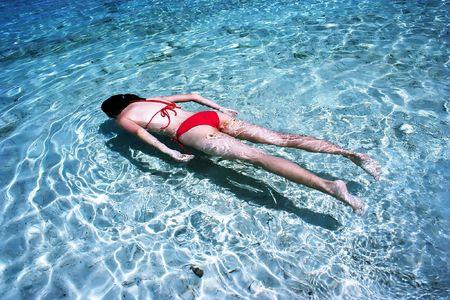 floating island: Bikini Girl Swimming at sea side.