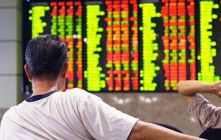 Asian man watching stock market index