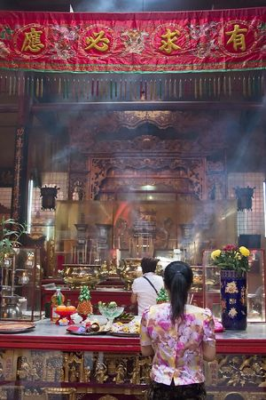 devout: Asian woman praying in a temple.