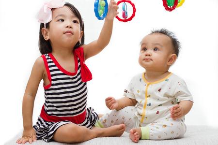 ni�as jugando: Dos ni�os chinos asi�ticos que juegan en el fondo blanco Foto de archivo