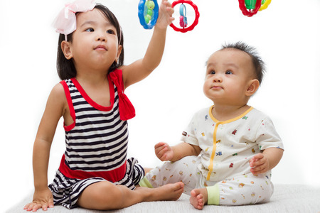 baby playing toy: Two Asian Chinese  children playing in white background