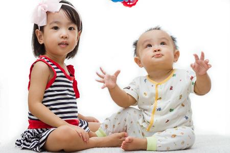 白い背景で遊ぶ 2 つのアジア中国の子供たち