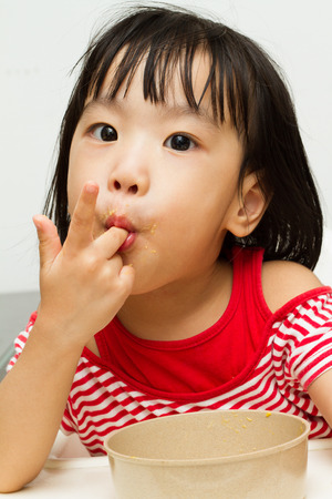 licking: Asian Chinese little girl eating durian fruit