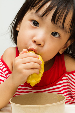 yummy: Asian Chinese little girl eating durian fruit