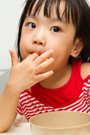 finger licking: Asian Chinese little girl eating durian fruit
