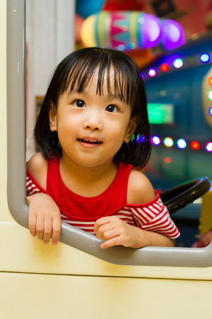 playcentre: Little Asain Chinese Bus Driver at indoor playground Stock Photo