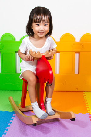 trojan: Asian Chiense girl riding trojan at indoor playground