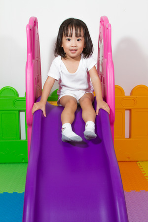 sliding: Asian Chiense girl sliding at indoor playground Stock Photo