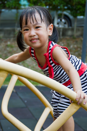 recreational climbing: Asian Chinese toddler girl climbing a ladder on the outdoor playground.