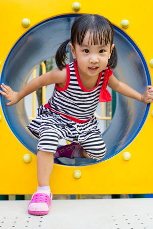 Asian Chinese kid crawling on outdoor playground tube. Stock Photo