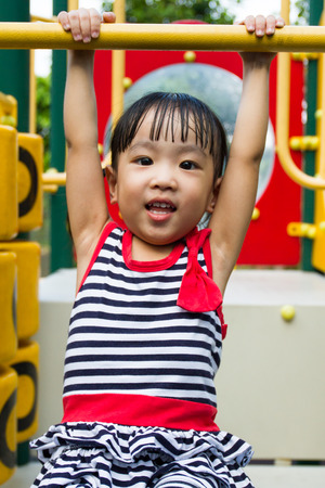 toddler playing: Asian Chinese little girl hanging on outdoor playground Stock Photo