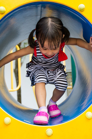 recreational: Asian Chinese kid crawling on outdoor playground tube. Stock Photo