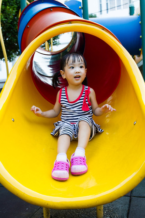 sliding: Asian Chinese little girl sliding on playground outdoor. Stock Photo